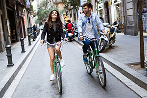 Couple qui fait su vélo en ville dans une petite rue